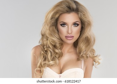 Portrait of sexy happy woman with long blonde curly hair in light lingerie. Studio shot.