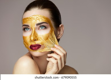 . Portrait Of Sexy Healthy Girl Removing, Peeling Cosmetic Gold Mask From Beautiful Face Skin