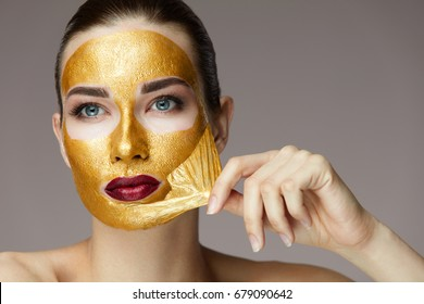 Portrait Of Sexy Healthy Girl Removing, Peeling Cosmetic Gold Mask From Beautiful Face Skin. 2