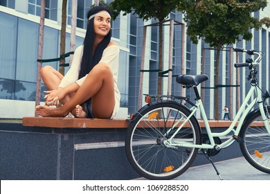 Portrait of a sexy hippie female wearing blouse and shorts in a headband, sits on a bench, crossed barefoot legs, near city bike against a skyscraper