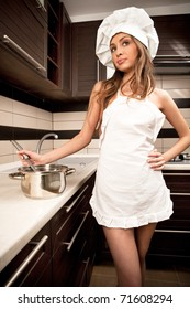 Portrait of sexy housewife tasting dish in kitchen room