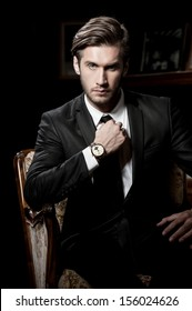 portrait of sexy macho man over dark background wearing a chronograph wrist watch