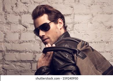 Portrait of sexy man looking over the shoulder. Having a bag on shoulder