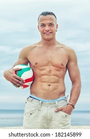 Portrait of sexy man posing on the beach with ball