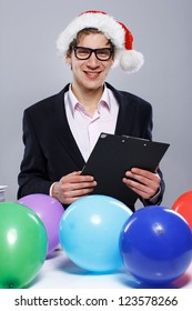 Portrait of sexy man posing in studio in front of table with color balloons
