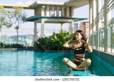 Portrait of a sexy meditation caucasian woman in a swimsuit sitting in lotus pose on the edge of a rooftop pool with green bushes and city views. Asia weekend.