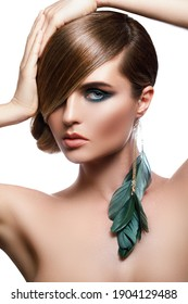 Portrait of sexy model in stylish image with sleek hair covering one eye and feather earring