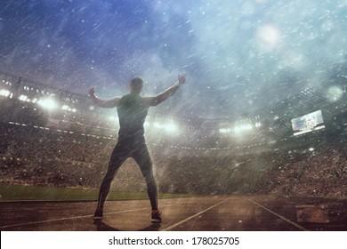 Portrait of sexy muscle man posing on stadium in epic rain
