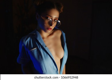 Portrait of a sexy nurse wearing glasses, on a dark background