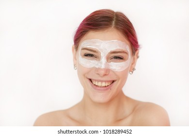 Portrait of a sexy and positive young woman with bare shoulders and a cosmetic white clay mask around her eyes looking with a smile on her face in a mirror against a white wall in a beauty salon