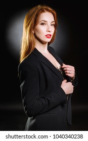 Portrait of a sexy red-haired girl on a black background. Beautiful business woman in a suit and shirt.