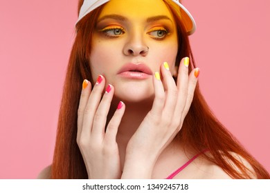 Portrait of a sexy red-haired girl in a transparent yellow sun visor isolated on a pink background.