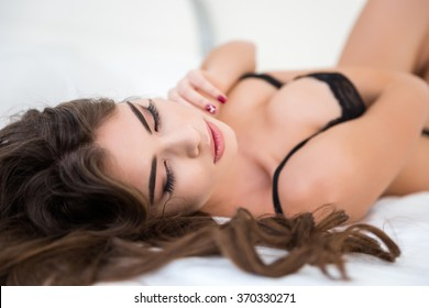 Portrait of a sexy relaxed woman in lingerie lying on the bed