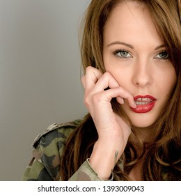 Portrait Of A Sexy Sensual Young Brunette Caucasian Woman, Wearing an Army Combat Jacket, Looking Thoughtful, Concerned And Nervous