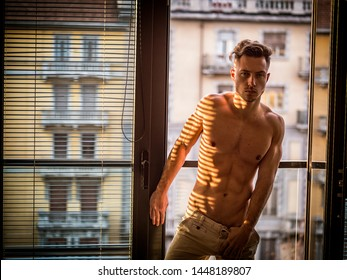 Portrait of sexy shirtless man covered with shadow stripes from window, looking at camera