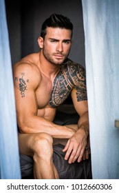 Portrait of sexy shirtless muscular man next to window curtains during the day, wearing only jeans