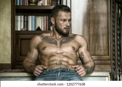Portrait of sexy shirtless muscular man sitting on stair steps during the day, wearing only jeans