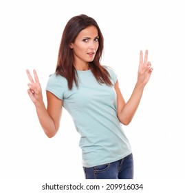 Portrait of sexy single woman on blue t-shirt with victory sign standing and smiling at you on isolated studio
