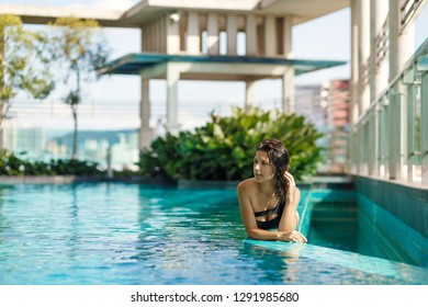 Portrait of a sexy smiling caucasian woman in a swimsuit lay on the edge of a rooftop pool with green bushes and city views. Asia weekend.