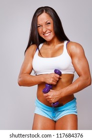 Portrait of sexy sport woman posing in studio with dumbbells