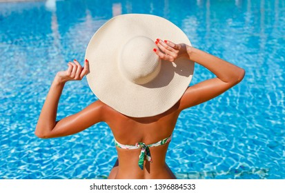Portrait of sexy tanned slim model woman in colorful bikini and hat having relax and enjoying in swimming pool. Hot summer day and bright sunny light. Luxury travel tropical resort concept