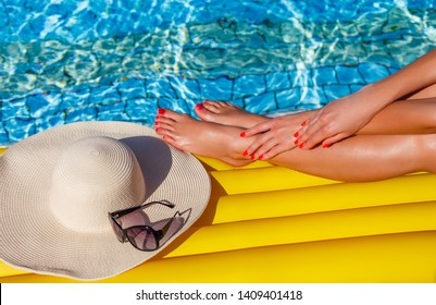 Portrait of sexy tanned slim model woman in colorful bikini and hat having relax and enjoying in swimming pool. Creative gel polish red pedicure and manicure. Luxury travel tropical resort concept