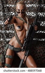 portrait of sexy topless blonde in sunglasses aiming a pistol against camouflage net