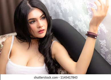 Portrait sexy woman. Attractive beautiful sexy girl is looking through window, curtain for seeing nice sky. Charming beautiful woman wear vest because it's hot weather in summer season. She look happy