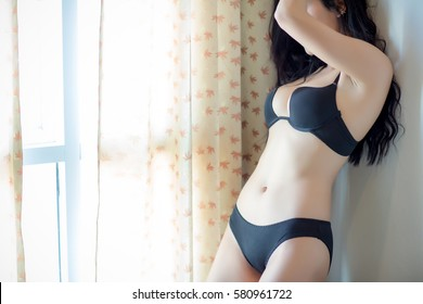 Portrait of sexy woman in black bra or underwear near window.Relaxing near window.Beautiful young woman in lingerie lying in room.
