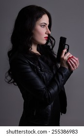 portrait of sexy woman in black with gun over grey background