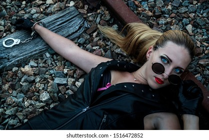 Portrait of a sexy woman in black leather clothes with handcuffs and sunglasses. Gangsta girl with red lips lying on the abandoned railway at night.