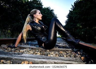 Portrait of a sexy woman in black leather clothes and gloves. Gangsta girl with red lips and blonde hair sitting on the abandoned railway.