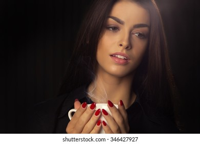 Portrait of sexy woman enjoying a hot cup of coffee on a dark background
