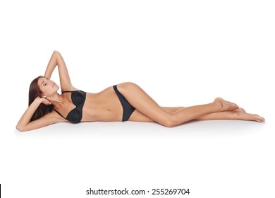 Portrait of a sexy woman lying down provocatively with closed eyes, isolated on white background