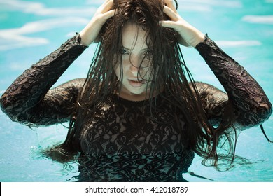 Portrait of the sexy woman relaxing in black fashion dress in pool. Creative photo session of beautiful Caucasian woman.