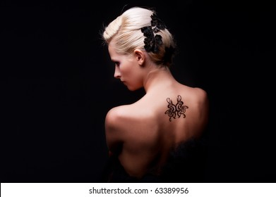 portrait of sexy woman with tattoo on her back