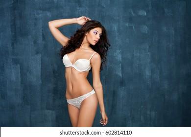 Portrait of sexy woman in white underwear on a dark wall