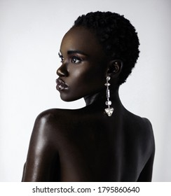 A portrait of a sexy young black female with short black hair and moist lip stick wearing a big diamond earring in front of a bright background.