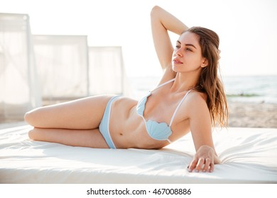Portrait of a sexy young brunette woman in bikini lying on bed and posing