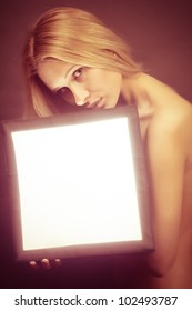 portrait of a sexy young female fashion model holds light box with copyspace