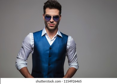 portrait of sexy young man with blue sunglasses and waistcoat standing on light grey background