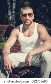 Portrait of a sexy young man in sunglasses with perfect muscular body
