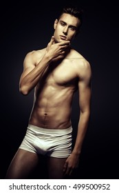 Portrait of a sexy young man in underwear. Studio shot over black background.