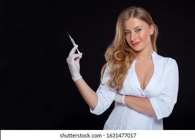 Portrait of sexy young nurse holding  syringe with a vaccine in hand isolated on a black background. She has long blond hair.