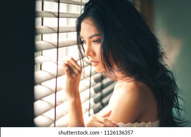 Portrait of sexy young woman looks through the jalousie