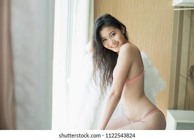 Portrait of sexy young woman model wearing bikini in the bedroom