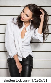 Portrait of sexy young woman posing in white shirt and black leather pants