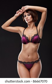 portrait of sexy young woman posing in magenta lingerie against black background