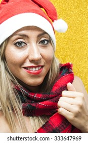 Portrait of Sexy Young Woman With Santa Claus hat and red plaid scarf Over Yellow Background