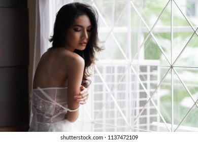 Portrait of sexy young woman in white dress posing near windows